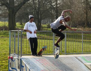 Birmingham, United Kingdom - March 14, 2014: Two skateboarders on a ramp, one performing a flip kick, the other leaning against the railings at the top watching with headphone's in his ears.